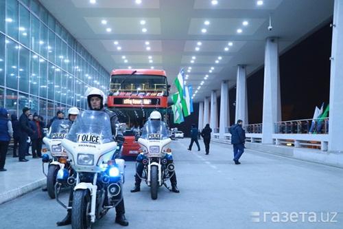 Xe cảnh sát dẫn đầu đoàn xe buýt hai tầng chở các cầu thủ đi từ sân bay về khách sạn Uzbekistan. Ảnh:
