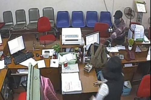 Tên cướp đeo khẩu trang, đội mũ lưỡi trai yêu cầu chuyển tiền vào chiếc ba lô gã mang theo.