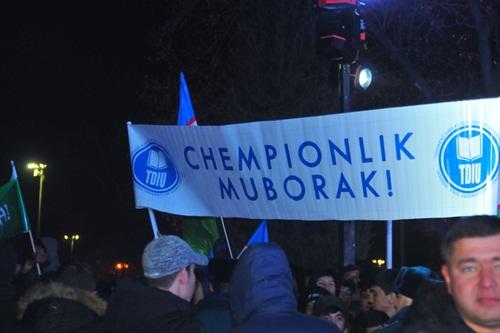Người dân vẫy cờ, biểu ngữ chào đón tuyển thủ trên đường xe chạy trong đêm. Ảnh: