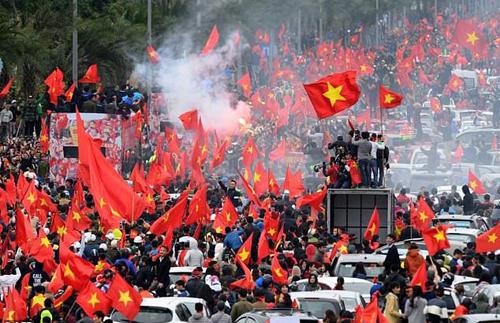 Biển người hâm mộ cầm quốc kỳ Việt Nam đi theo chiếc xe bus hai tầng chở các tuyển thủ U23 diễu hành trên đường phố Hà Nội vào ngày 28/1. Ảnh: AFP.