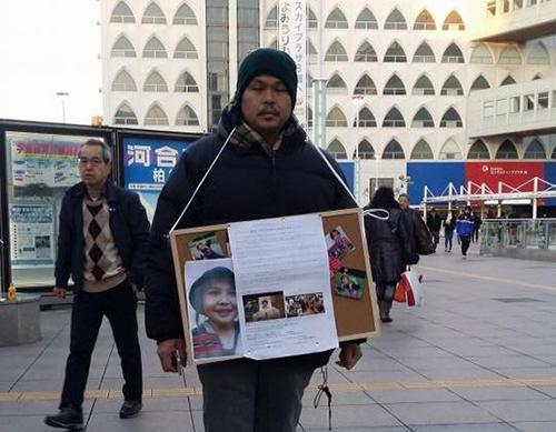 Cha của bé Nhật Linh, anh Lê Anh Hào, xin chữ ký tại ga Kashiwa, Chiba, Nhật Bản. Ảnh:Facebook/Nguyễn Thị Nguyên.