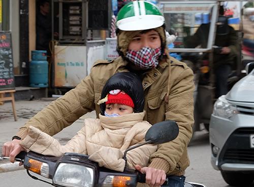 Phụ huynh ủ ấm con khi đưa tới trường mầm nonsáng 30/1. Ảnh: Quỳnh Trang.