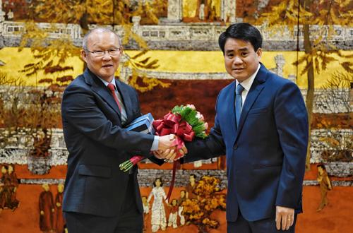 Chủ tịch UBND TP Hà Nội Nguyễn Đức Chung (phải) tặng hoa và quà cho HLV Pask Hang-Seo. ảnh: Giang Huy.