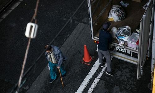 Đội xử lý chất những đồ đạc thu được từ căn hộ của ông Hiroaki lên xe tải để chuẩn bị chở đi. Ảnh: Washington Post.