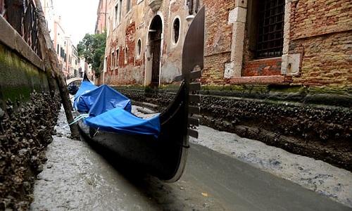 Một con thuyền đáy bằng phủ bạt nằm bất động vì không thể di chuyển trên lòng kênh khô cạn. Ảnh: AFP.