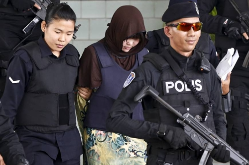 Vietnamese Doan Thi Huong, second from left, is escorted by police as she leaves after a court hearing at Shah Alam court house in Shah Alam, Malaysia, on Tuesday. | AP