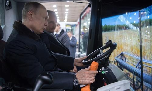 Tổng thống Nga Vladimir Putin trải nghiệm thiết bị mô phỏng máy gặt trong chuyến thăm nhà máy hôm 2/2. Ảnh: Sputnik.
