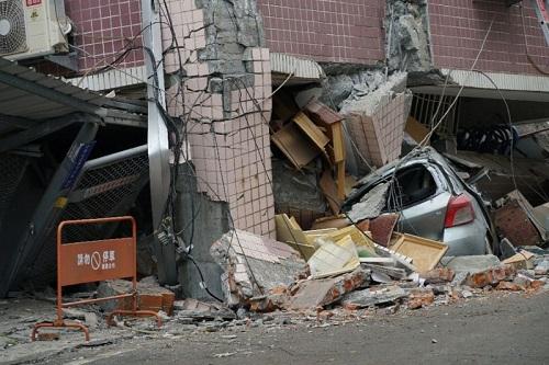 Ôtô bẹp rúm dưới tòa nhà đổ. Ảnh: AFP.