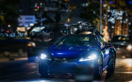 Siêu nhân Báo đen bám trên nóc chiếc coupe trong một cảnh rượt đuổi trong phim. Ảnh: Lexus.