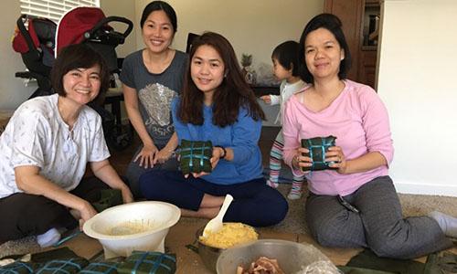 Chị Huỳnh Thu, vợ anh Dũng, thứ hai từ trái sang, cùng nhóm bạn ở California gói bánh chưng đón Tết Mậu Tuất. Ảnh: NVCC.