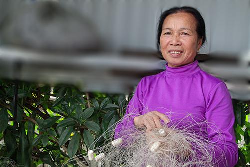 Bà Tâm bên tấm lưới cũ từng bắt được cá sủ vàng 23 năm trước. Ảnh:Đức Hùng