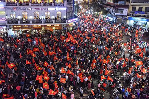 Người dân và du khách mừng chiến thắng của đội tuyển U23 Việt Nam tại quảng trường Đông Kinh Nghĩa Thục tối 23/1. Ảnh: Giang Huy.