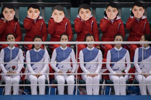 Đội cổ vũ Triều Tiên đeo mặt nạ có hình một thanh niên ngày 10/2. Ảnh: AFP.