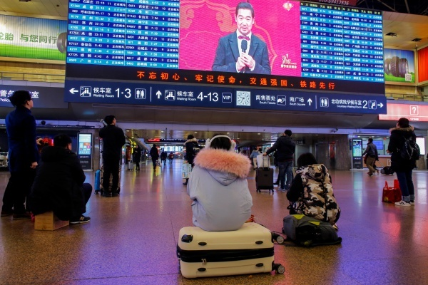 [Caption]People watch the CCTV Spring Festival Gala TV show on a screen at the Beijing West train station in Beijing