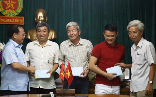 Ông Tất Thành Cang (bên trái) khen thưởng lực lượng công an tham gia phá án. Ảnh: Quốc Thắng.