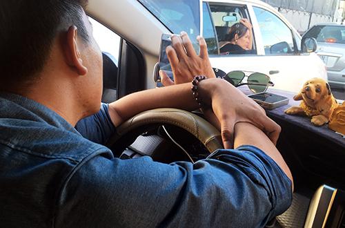 Nhiều tài xế lướt điện thoại trong lúc kẹt xe. Ảnh: Hoàng Nam.