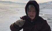 Bà lão Siberia trượt băng qua hồ sâu nhất thế giới đi chăm bò