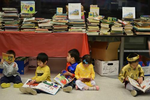 Các em bé háo hức với sách truyện tiếng Anh.