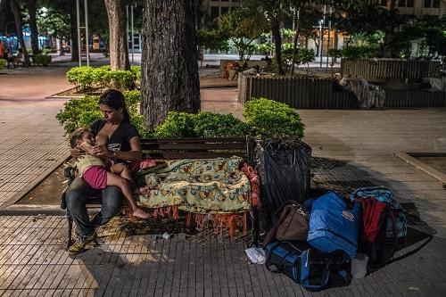 Hernandez cho con gái hai tuổi bú sữa, trong lúc ngồi trên chỗ ngủ tạm bợ xung quanh đầy rác. Bà mẹ trẻ đã phải bán mái tóc dài lấy tiền mua thức ăn.Ảnh: NYT.