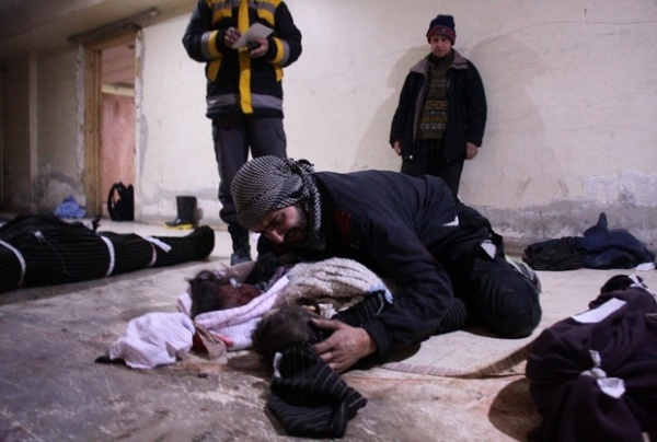Man weeps over his child who was killed in air strikes on the besieged Eastern Ghouta, 19 February (AFP)