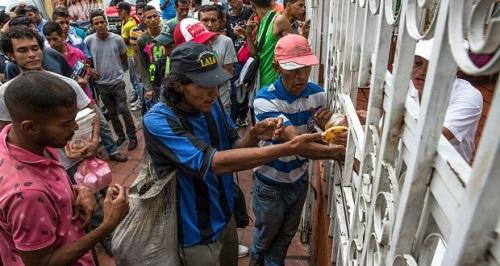 Người Venezuela xếp hàng xin cơm từ thiện từ một tổ chức phi lợi nhuận ở Cucuta. Ảnh: NYT.