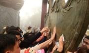 Người dân xoa tiền trên chùa Đồng ở Yên Tử để cầu may