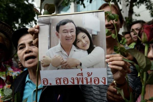 Người ủng hộ cầm ảnh ông Thaksin và em gái Yingluck tại Bangkok hồi tháng 5/2017. Ảnh: