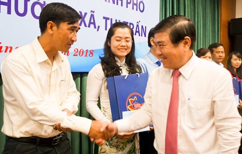 Chủ tịch UBND TP HCM Nguyễn Thành Phong khen thưởng lãnh đạo các phường có thành tích thi đua xuất sắc năm 2017. Ảnh: Tuyết Nguyễn.
