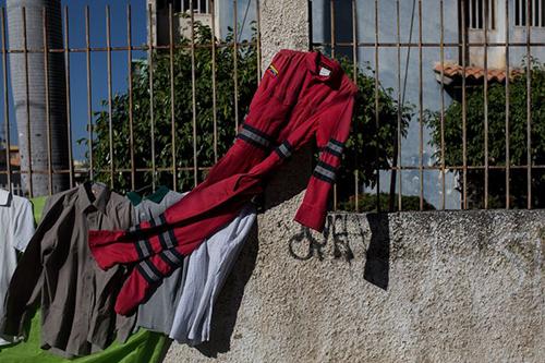 Công nhân củatập đoàn dầu khí quốc giaPetroleos de Venezuela mang đồ bảo hộ ra vỉa hè bán lấy tiền mua thức ăn. Ảnh: Bloomberg.