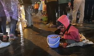 Nhiều người bế trẻ nhỏ đội mưa ăn xin trong phiên chợ ở Nam Định