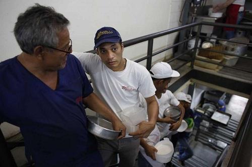 Người lao động tại một tiệm bánh ở Caracas. Đối với họ, hai bữa cơm miễn phí mỗi ngày là lý do để tiếp tục làm công việc được trả thấp hơn lương tối thiểu 30% này. Ảnh: AP.