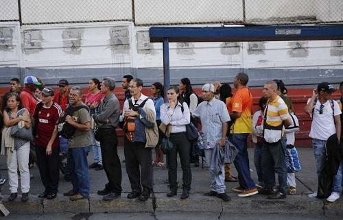 Người dân chờ xe buýt ở Caracas. Ảnh: AP.