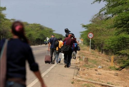 Đoàn người di cư đi bộ trên một cao tốc ởParaguachon, sau khi ra khỏi biên giới Venezuela - Colombia hôm 16/2. Ảnh: Reuters.