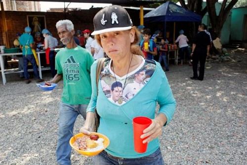 Một phụ nữ vẻ mặt đầy mệt mỏi cầm trên tay suất ăn từ thiện của một nhà thờ Công giáo tại Cucuta, Colombia hôm 21/2. Ảnh: Reuters.