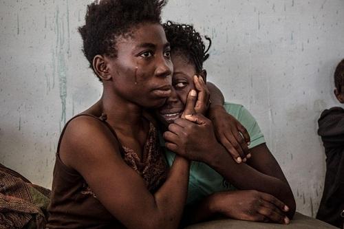 Haingười tị nạnNigeria ôm nhau khóc trong một trung tâm giam giữ ở Surman, Libya hồi tháng 8/2016. Ảnh: Reuters.