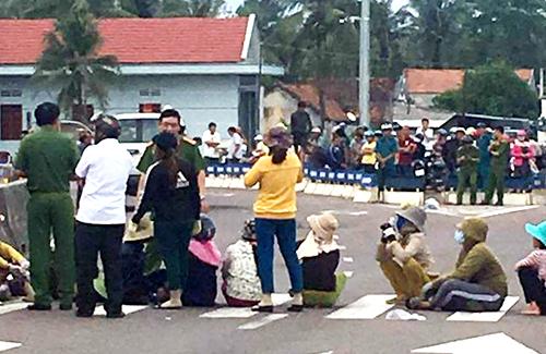 Người dân ngồi bệt trên quốc lộ phản ứng dự án nhà máy chế biến hải sản. Ảnh: Người dân cung cấp.