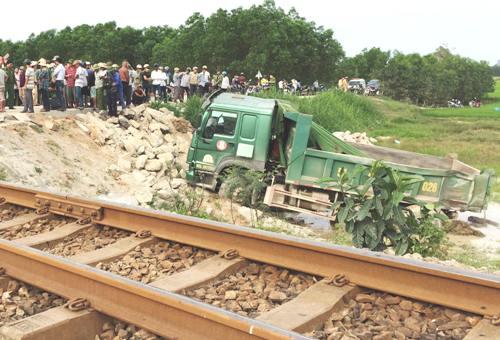 Ôtô tải chở đá bị tàu hỏa hất văng xuống ruộng. Ảnh: Thạch Thảo.