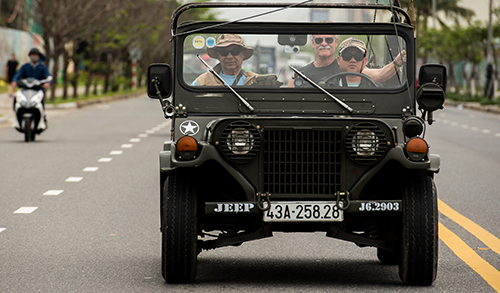 Các cựu binh MỹJorge Azpeita (trái)vàSteven Haas ngồi trên xe Jeep đi thăm Đà Nẵng hôm 25/2. Ảnh: Stars and Stripes