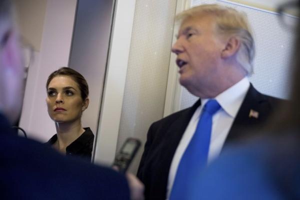 Tổng thống Mỹ Donald Trump trả lời báo chí trên chuyên cơ khi Hope Hicks đứng bên cạnh. Ảnh: AP.