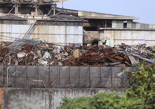 Nhiều tấn phế liệu được đổ sát tường rào của nhà máy thép giáp với khu dân cư ở Hòa Liên. Ảnh: Nguyễn Đông.