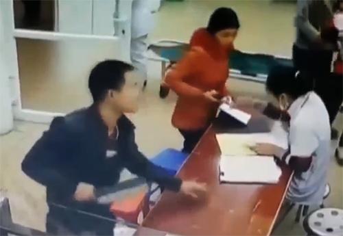 Nam thanh niên cầm con dao mới mua đe dọa các bác sĩ. Ảnh chụp từ clip