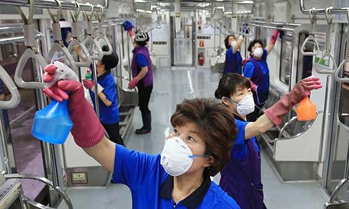 Nhân viên dọn vệ sinh trên tàu điện ngầm ở Seoul, Hàn Quốc. Ảnh: AFP.