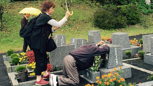 Ông Ngô Gia Khánh gục trước mộ chatrong chuyến thăm Nhật tháng 10/2017. Ảnh: NHK World