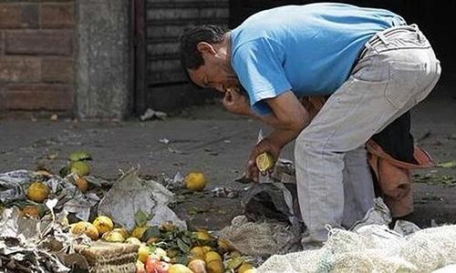 Một người đàn ông bới rác tìm thức ăn ở thủ đô Caracas, Venezuela. Ảnh: Cuba Quarter.