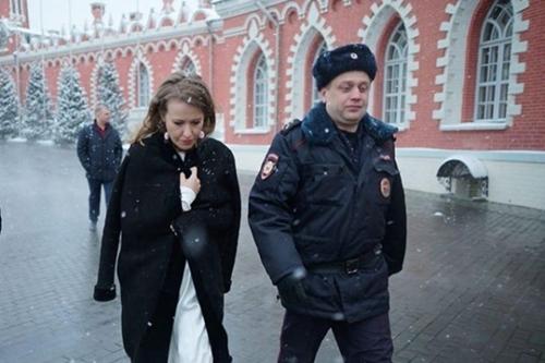 bà Sobchak đi cùng cảnh sát sau khi bị dội nước.