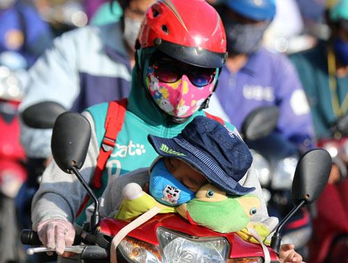 Năm nay, phụ huynh phải ký cam kết với trường đội mũ cho con khi chạy xe máy. Ảnh: Quỳnh Trần.