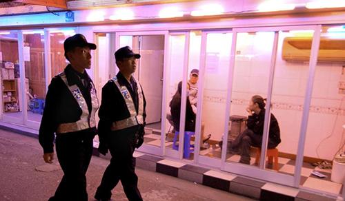 Cảnh sát Hàn Quốc đi qua phố đèn đỏ ở Seoul. Ảnh: AFP