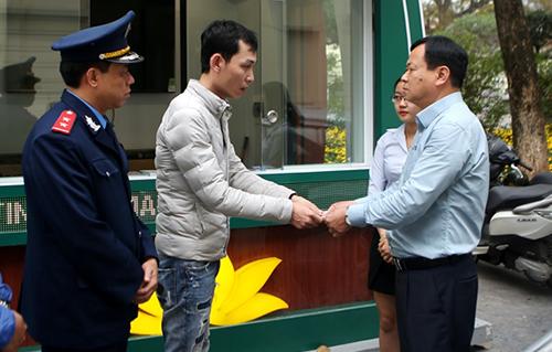 Tài xế Điệp thứ hai từ trái qua trả lại tiền thừa cho du khách thông qua đại diện của Thanh tra Sở Du lịch Hà Nội. Ảnh: KTĐT