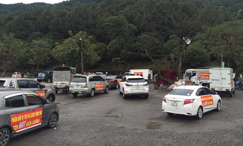 Hàng chục chiếc xe ô tô đỗ tại khu vực chùa Cái Bầu, huyện Vân Đồn sáng 8/3, được dán băng rôn khẩu hiệu phản đối trạm thu phí BOT Biên Cương. Ảnh: Minh Cương