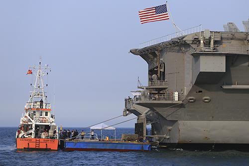 Việc di chuyển từ tàu sân bay vào đất liền phải có tàu nhỏ hỗ trợ. Ảnh: Nguyễn Đông.